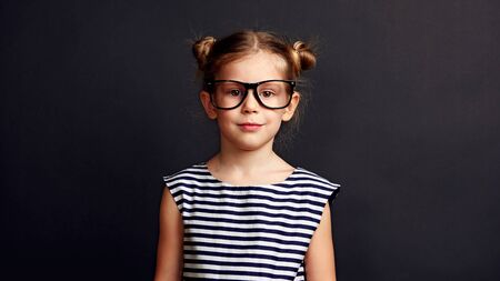 Portrait of pretty schoolgirl in glasses over black background.