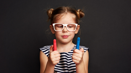 Portrait of thinking girl holding colorful pencils over black background. Stock fotó