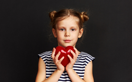 Adorable girl holding red heart over dark background. Concept of love, help and protection.