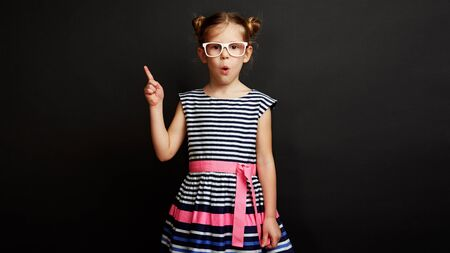 Childs inspiration concept. Smart surprised schoolgirl standing with finger up over dark background. Stock fotó