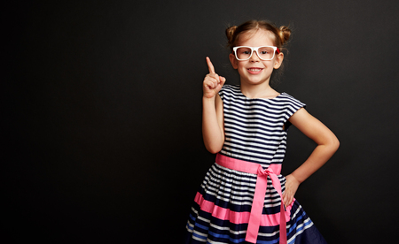 Pretty smiling girl in eyeglasses pointing over black background. Joyful child in stylish dress having creative idea.