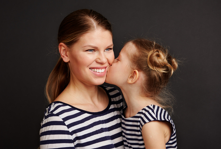 Petty girl kissing her mother. Beautiful female smiling and hugging her daughter.