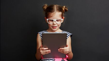 Adorable girl playing game on digital tablet over dark background. Technology and lifestyle. Stock fotó