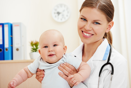 Young nurse holding adorable little child in doctors office.