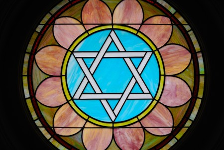 judaica: Colorful stain glass image of a Star of David in a synagogue.