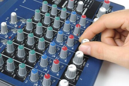 preamp: A and twisting a knob on a mixing board of a preamp. Stock Photo