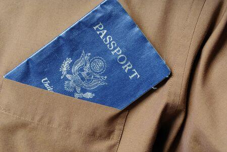 Passport sticking out of a pocket of a  brown shirt.