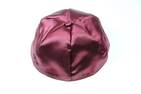 yarmulke: A purple yarmulke, a Jewish head covering, on white.