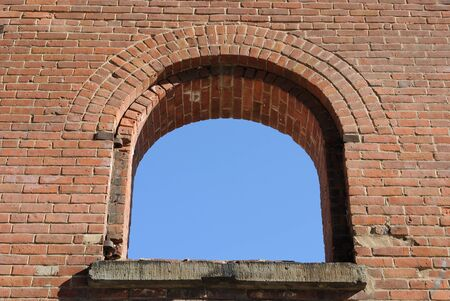 a window to the sky on a gritty brick building.