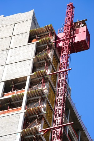 A building under construction with an elevator lift. Stock Photo