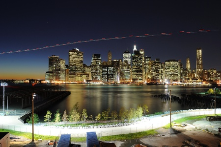 Lower Manhattan at night from the Brooklyn Heights Promenade as a helicopter flies by. Stock Photo
