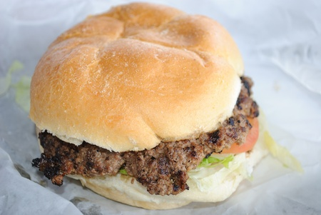 A fast food style hamburger unwrapped.