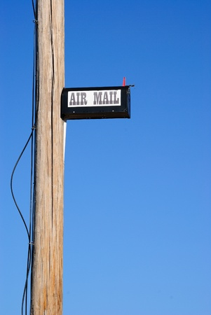 humor: A mailbox humorously placed high on a telephone pole.