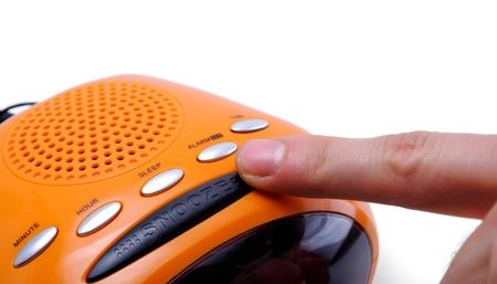 Finger pressing a snooze alarm button