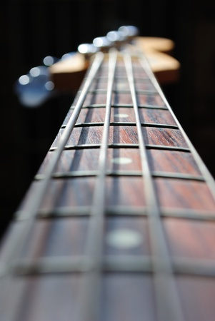frets: abstract view of a bass guitar neck with a shallow depth of field, focus on the middle inlayed fret.