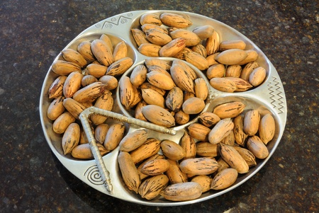 nut cracker: Organic pecans still in their shells on a fancy plate with nut cracker.