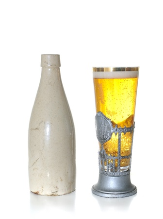 Old Ceramic Bottle and Beer in a uniqe stein glass isolated on a white background.