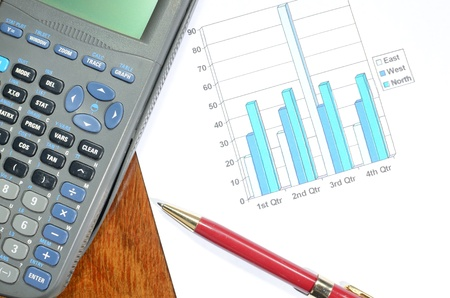scholarly: Graph, calculator, and pen on a table indicating office work.