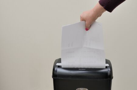 Hand putting paper into a shredder photo