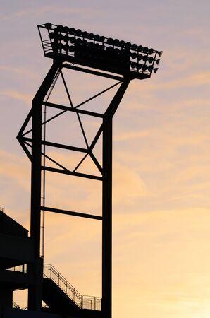floodlights: Silhouette of Stadium Floodlights against a fiery sky. Stock Photo