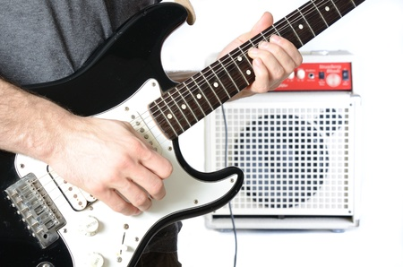 Guitarist playing a solo with the amp in the background. photo
