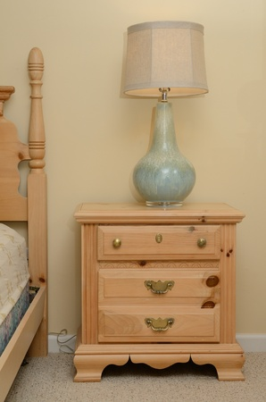 bedside: bedside table with lamp and wooden furniture