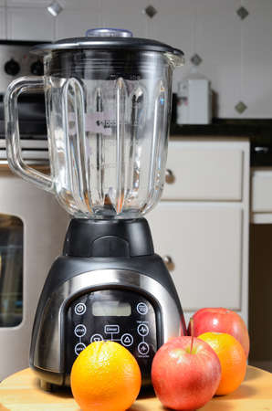 home appliances: Blender with whole raw fruit with a kitchen background. Stock Photo