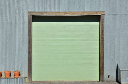 A green garage door at a warehouse. Stock Photo - 9185454