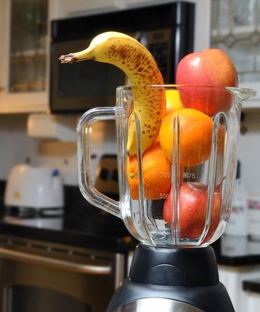 licuadora: Mezclador con fruta todo crudo con un fondo de cocina. Foto de archivo