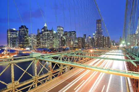 View of downtown Manhattan from the Brooklyn Bridge with traffic flying by. photo