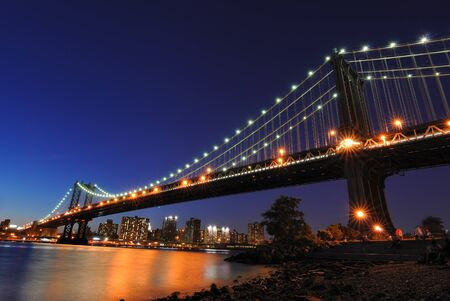 eastriver: The Manhattan Bridge illuminated at night spanning the East River in New York city. Stockfoto
