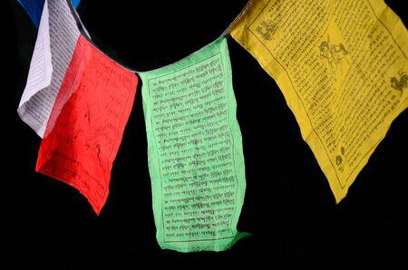 sanskrit: Tibetan prayer flags isolated on black.