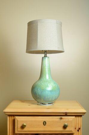 bedside: A lamp on a wooden endtable.
