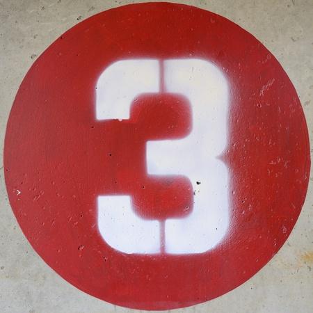 콘크리트 벽에 빨간색 원 안에 숫자 3 스톡 콘텐츠