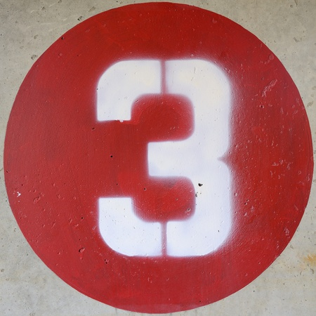 round: number 3 in a red circle on a concrete wall Stock Photo