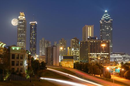 Skyline of downtown Atlanta, Georgia from above Freedom Parkway with a full moon. Stock Photo