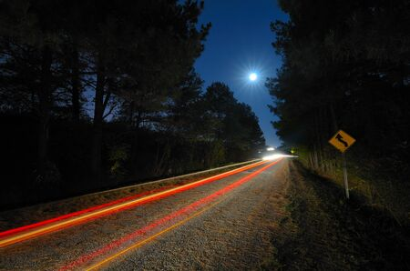Cars pass on a country road at night with the moon above Stock Photo