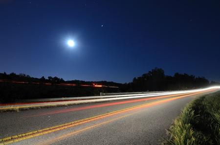 Autos passieren auf einer Landstraße in der Nacht mit dem Mond oben