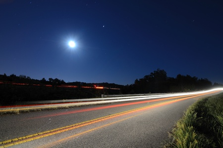 night street: Cars pass on a country road at night with the moon above Stock Photo