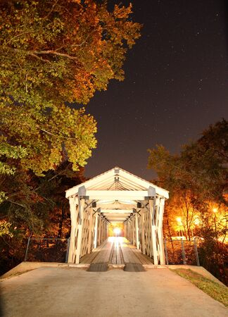 An old wooden covered bridge under the night sky photo