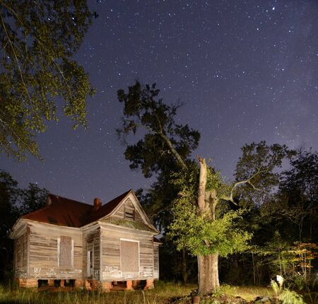 stargazing: a scary abandoned house under a starry sky Stock Photo