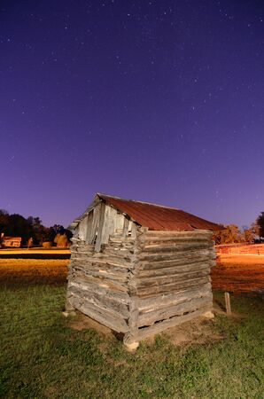 An old wooden tool shed under the night sky Фото со стока