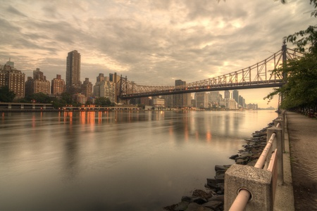 Queensboro Bridge Spanning the East River in New York City on a cloudy morning.