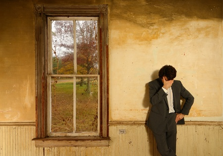 Man wearing a suit in despair props his head against his hand in an old fashioned abandoned home Stock Photo - 11511142