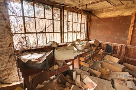Old office in a factory, abandoned, ransacked, and overgrown with vines. Editorial