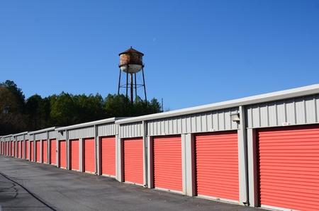 Hilera de unidades de almacenamiento con la torre de agua en el fondo Foto de archivo - 11890574