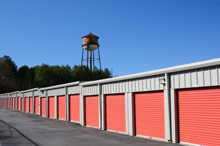 storage: Row of storage units with water tower in the background Stock Photo