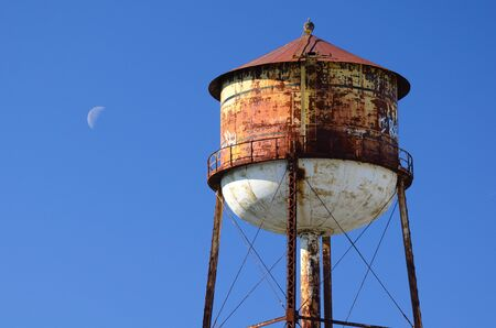 Rusty water tower in a cloudless sky with crescent moon Stock Photo - 11890567