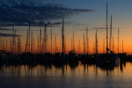 docked boats silohuetted against the morning sky photo