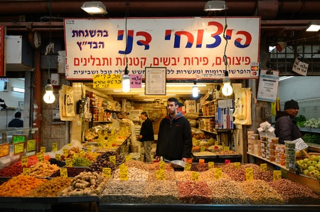 Jerusalem, Israel - February 16, 2012: An Israeli vendor sells dried fruits and nuts in a Jerusalem shook. Editöryel